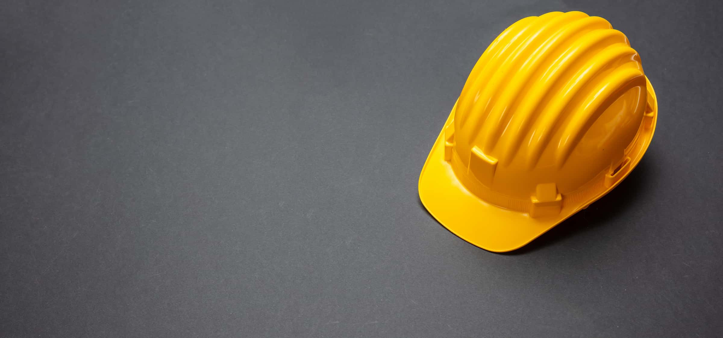 construction-project-safety-yellow-hard-hat-on-bla-NG9BPZS (1)